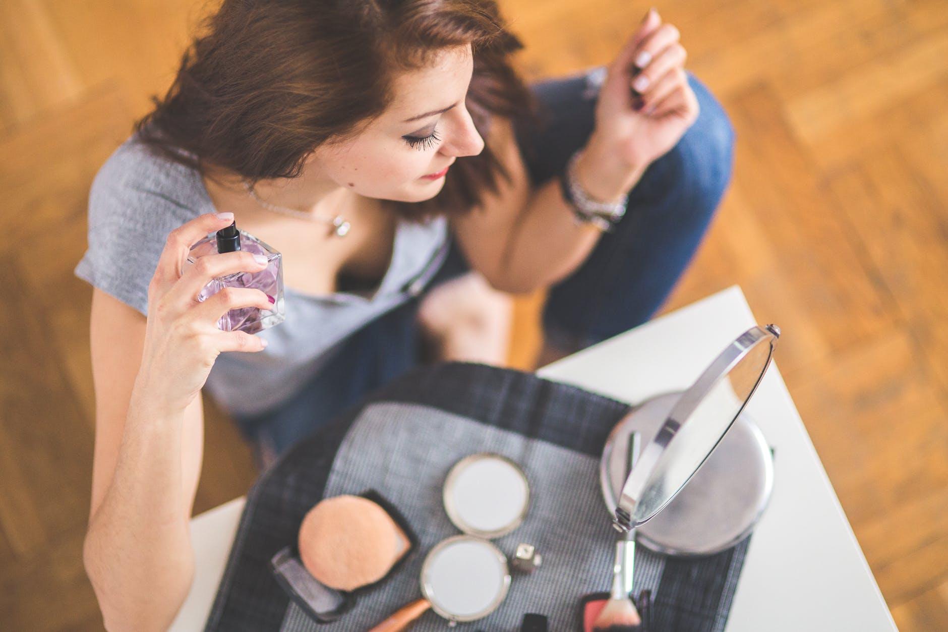 closeup of a young woman applying perfume